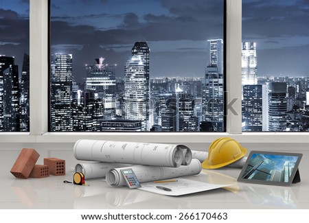 work tools in architect's office with city skyline - stock photo