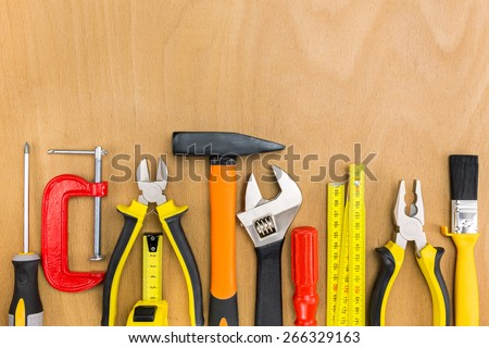 Work tools lined up in a straight line on wooden background - stock photo