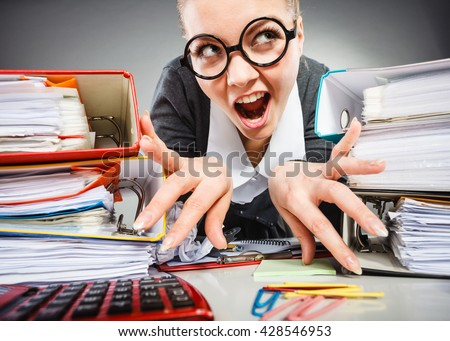 Workaholism mental insanity weird job work company concept. Insane office woman at work. Mad secretary making silly expression lurking through her desk. - stock photo