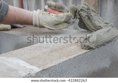 worker aligns with a spatula, lay brick cinderblocks. - stock photo