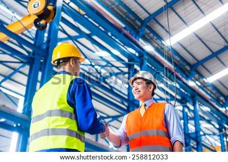 Worker and customer having agreement in factory shaking hands - stock photo