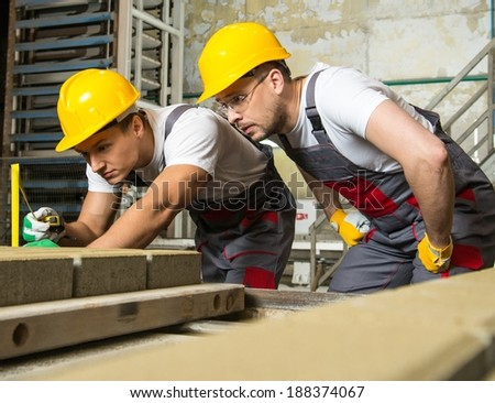 Worker and foreman in a safety hats performing quality check on a factory   - stock photo