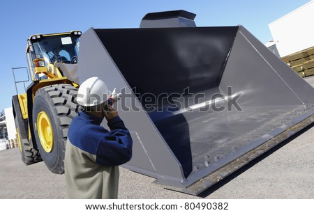 worker and giant bulldozer, digger, construction and excavating machinery - stock photo