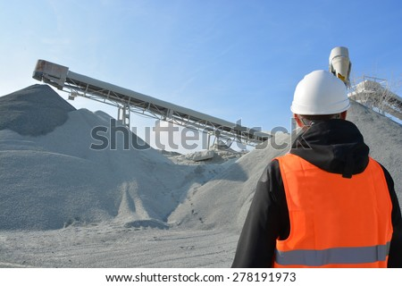 Worker and heavy machine for gravel production in background - stock photo