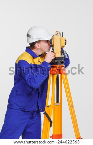 worker and theodolite  - stock photo