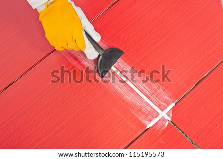 worker applies  grout whit rubber trowel red tiles - stock photo