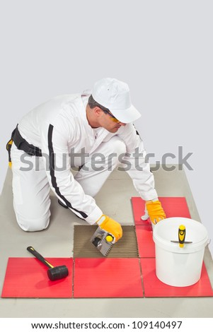 Worker Applies Tile Adhesive with Notched Trowel Tile on a Floor before tilling - stock photo