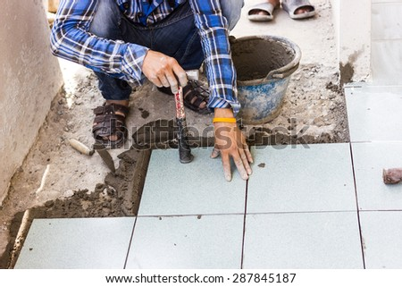 Worker are floor tiles. - stock photo
