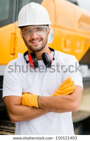 Worker at a construction site working with heavy machines  - stock photo