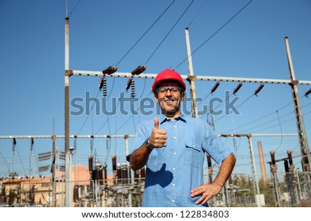 WORKER AT AN ELECTRICAL SUBSTATION. Thumb up given by smiling engineer next to electrical substation. Selective focus. - stock photo