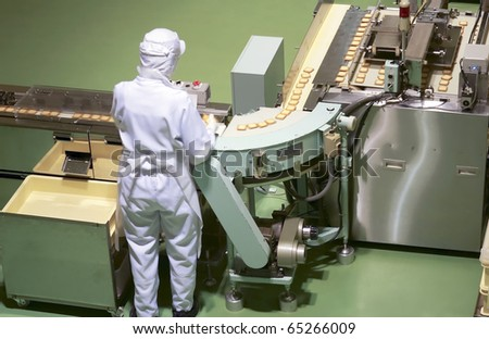 worker behind the conveyor in shop of confectionery factory - stock photo