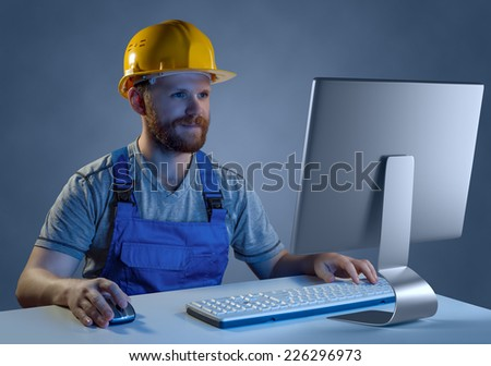 worker builder in helmet and uniform working at a computer, purchase in online store - stock photo