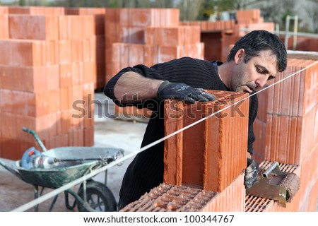 Worker building a wall - stock photo