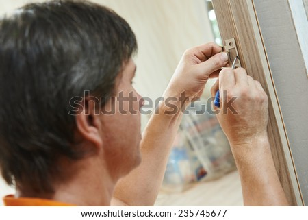 worker carpenters at wooden  internal door lock installation - stock photo