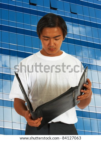 Worker Checking His Notes In A Leather Folder And Standing In Front Of A Downtown Office Building - stock photo