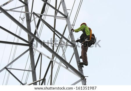 worker climbing on transmission line tower - stock photo