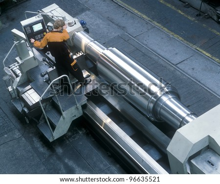 Worker controlling a big lathe - stock photo