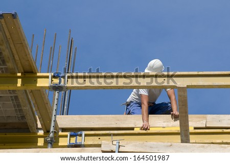 Worker controlling the level of wooden framework in a building under construction - stock photo