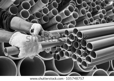 Worker cut pvc pipe in construction site - stock photo