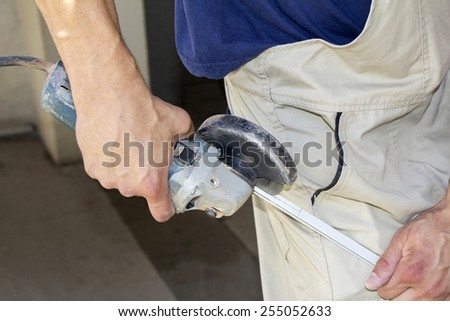 Worker cutting aluminum with angle grinder in workshop - stock photo