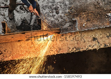 worker cutting metal and sparks spread - stock photo