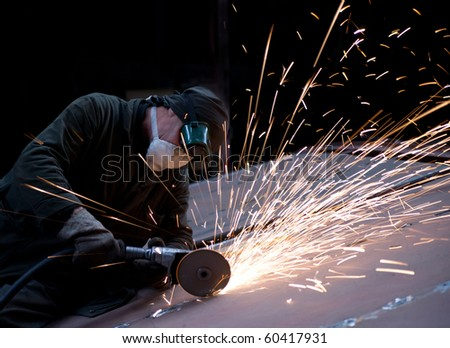 Worker cutting metal using rotary disc - stock photo