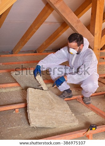 Worker cutting mineral wool panel installing thermal insulation on a building - stock photo