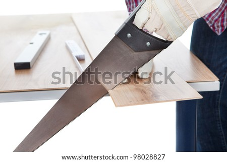 Worker cutting piece of laminate using hand saw - stock photo
