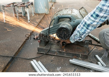Worker cutting steel tube with spark. - stock photo