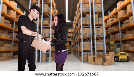 Worker delivering a parcel to young woman in a distribution warehouse - stock photo