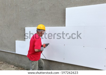 Worker drilling styrofoam sheet insulation on the wall - stock photo