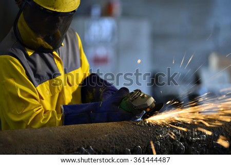 Worker during use electric wheel grinding on steel structure in factory work shop. - stock photo
