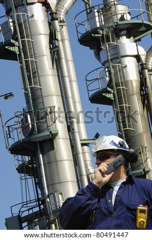 worker, engineer, chemical-worker, standing in front of large refinery oil towers - stock photo