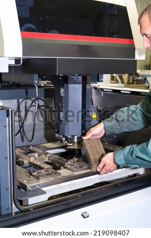 Worker examining metal detail in cnc industrial machine in workshop. Metalworking and engineering industry, lathe , cnc and milling technology. - stock photo