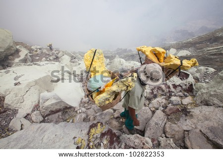 Worker,Extracting sulphur inside Kawah Ijen crater, Indonesia - stock photo