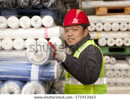Worker factory textile arranging fabric in warehouse looking at you camera - stock photo