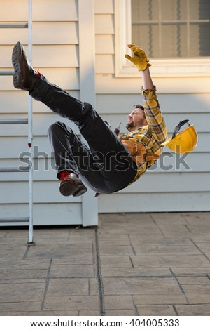 Worker falling from ladder onto floor - stock photo