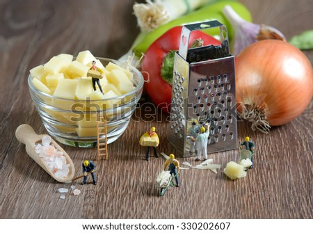 Worker figurines making pizza - stock photo