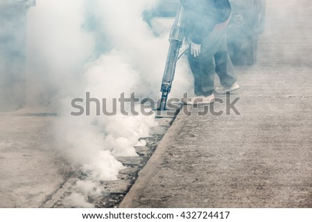 Worker fogging street drain with insecticides to kill aedes mosquito breeding ground, carrier of dengue and Zika virus. - stock photo