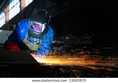 worker grinding/welding metal and sparks spreading - stock photo