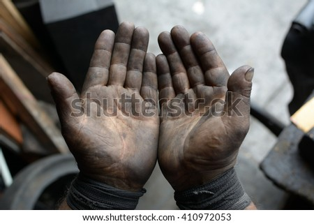 Worker hand covered with oil - stock photo