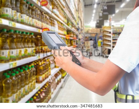 worker hand lady scanning package with warehouse barcode scanner in modern storehouse - stock photo