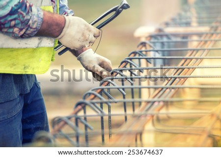 worker hands using steel wire and pliers to secure bars on construction site and preparing for concrete pouring - stock photo