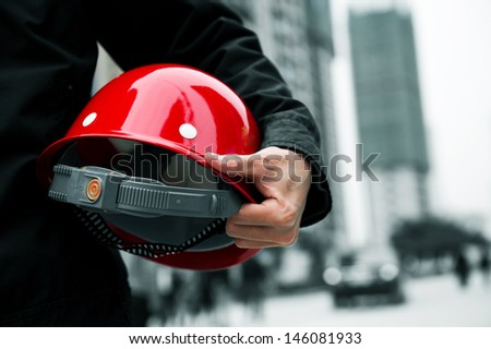 Worker holding a helmet with background of  blurred construction site.  - stock photo