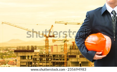 Worker holding a helmet with background of construction site. - stock photo