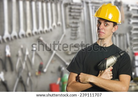 Worker holding electric drill and wearing hard hat - stock photo