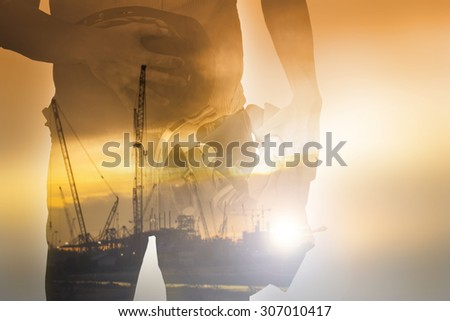 Worker holding tool with Twilight time on Labour Day ,double exposure  - stock photo