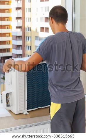 Worker holds the outdoor unit of the air conditioner - stock photo