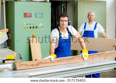 worker in a carpenter's workshop using saw machine - stock photo