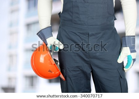 Worker in a construction site holds a helmet - stock photo